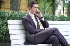 Młody człowiek w garniturze opuszczał biuro i przychodził park siedzi na białej ławce samotnie i opowiada na telefonie fotografia stock