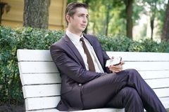 Młody człowiek w garniturze opuszczał biuro i przychodził park siedzi na białej ławce samotnie i opowiada na telefonie zdjęcia royalty free