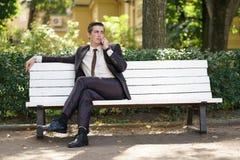 Młody człowiek w garniturze opuszczał biuro i przychodził park siedzi na białej ławce samotnie i opowiada na telefonie zdjęcie stock