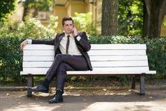 Młody człowiek w garniturze opuszczał biuro i przychodził park siedzi na białej ławce samotnie i opowiada na telefonie obraz stock