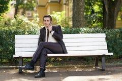 Młody człowiek w garniturze opuszczał biuro i przychodził park siedzi na białej ławce samotnie i opowiada na telefonie obrazy stock