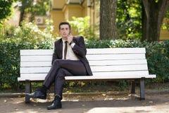 Młody człowiek w garniturze opuszczał biuro i przychodził park siedzi na białej ławce samotnie i opowiada na telefonie zdjęcie royalty free
