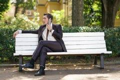 Młody człowiek w garniturze opuszczał biuro i przychodził park siedzi na białej ławce samotnie i opowiada na telefonie zdjęcia stock