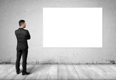 Młody człowiek w garniturze, stoi przód betonowa ściana z białą puste miejsce deską na nim zdjęcia stock