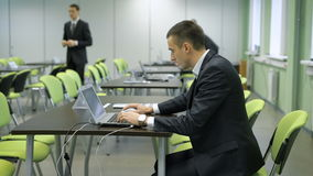 Młody człowiek w garniturze z drogim wristwatch pracuje z laptopu obsiadaniem na zielonym krześle za czarnym biurkiem zdjęcie wideo