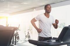 Młody człowiek w gym biegającym na karuzeli Zdjęcia Royalty Free