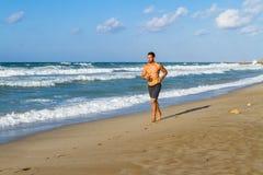 Młody człowiek w jego latach dwudziestych jogging na piaskowatej plaży Zdjęcia Stock