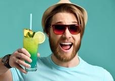 Młody człowiek w kapeluszowego i czerwonego okulary przeciwsłoneczni chwyta margarita koktajlu napoju soku szczęśliwy ono uśmiech Fotografia Stock