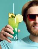 Młody człowiek w kapeluszowego i czerwonego okulary przeciwsłoneczni chwyta margarita koktajlu napoju soku szczęśliwych otuchach Zdjęcie Stock