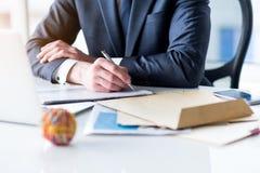 Młody człowiek w kostiumu pracuje w biurze Zdjęcie Royalty Free