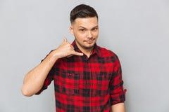 Młody człowiek w koszulowym seansu telefonu znaku Zdjęcia Stock