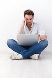 Młody człowiek w krawieckiego siedzenia wyszukuje internecie Zdjęcia Royalty Free