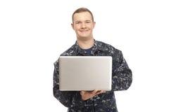 Młody człowiek w marynarka wojenna jednolitym używa laptopie Obrazy Stock