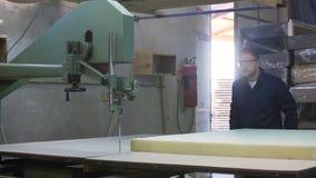Młody człowiek w meblarskiej fabryce ciie pianę dla kanapy zbiory wideo