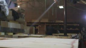 Młody człowiek w meblarskiej fabryce stosuje kleidło na drewnianym kawałku kanapa zdjęcie wideo