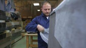 Młody człowiek w meblarskiej fabryce stosuje pianę na kawałku kanapa zbiory