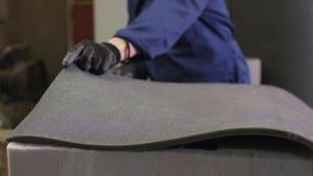 Młody człowiek w meblarskiej fabryce stosuje pianę na kawałku kanapa zdjęcie wideo
