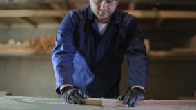 Młody człowiek w meblarskim fabrycznym rozcięciu drewniani kawałki dla kanapy zbiory wideo