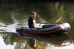 Młody człowiek w nadmuchiwanej łodzi z połowem przy rzeką Obraz Royalty Free