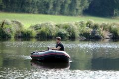 Młody człowiek w nadmuchiwanej łodzi z połowem przy rzeką Zdjęcie Stock