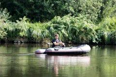 Młody człowiek w nadmuchiwanej łodzi z połowem przy rzeką Fotografia Stock