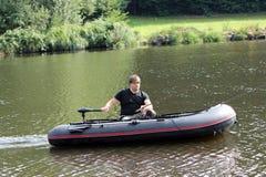 Młody człowiek w nadmuchiwanej łodzi z połowem przy rzeką Obrazy Royalty Free