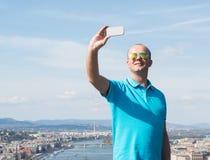 Młody człowiek w okularach przeciwsłonecznych bierze selfie fotografia stock