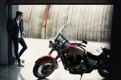 Młody człowiek w okularach przeciwsłonecznych i skórzanej kurtki pozycja w garażu z motocyklem Obraz Royalty Free