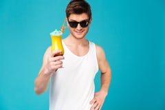 Młody człowiek w okularach przeciwsłonecznych pokazuje koktajl Zdjęcia Royalty Free
