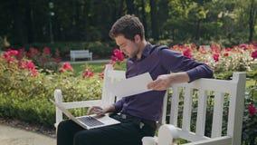 Młody człowiek w parku używać papier i laptop zdjęcie wideo