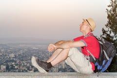 Młody człowiek w plecaka i kapeluszu obsiadaniu na tle ogromne miasto below Boczny widok Obraz Royalty Free