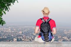 Młody człowiek w plecaka i kapeluszu obsiadaniu na tle ogromne miasto below widok z powrotem Fotografia Royalty Free