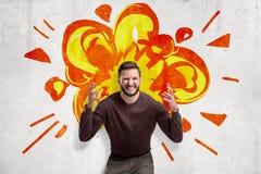 Młody człowiek w przypadkowych ubraniach robi móżdżkowemu wybuchowi gestykuluje z kreskówka wybuchem rysującym na biel ściany tle obrazy royalty free
