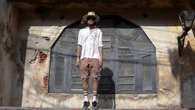 Młody człowiek w słomianym kapeluszu i okularach przeciwsłonecznych skacze P?tla materia? filmowy zbiory