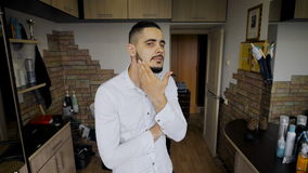 Młody człowiek w salon fryzurach Modniś z nowym ostrzyżeniem i brodą, studiuje rezultat i zadawalający zdjęcie wideo