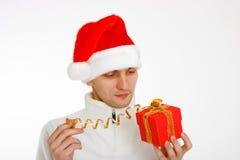 Młody człowiek w Santa kapeluszowym mienia prezencie obraz stock