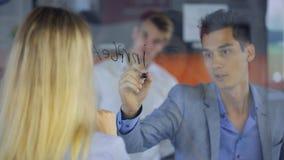 Młody człowiek w szarej kostium kurtce, pisze markiera na przejrzystej desce która stoi przed blond kobietą, zbiory