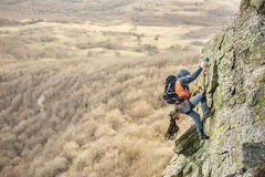 Młody człowiek wspina się skałę na arkanie z zbawczymi paskami ubezpieczenie i arkana, w pełnym mountaineering wyposażeniu i a obraz stock