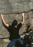 Młody człowiek wspinaczka na skale w małym pęknięciu w kamieniu fotografia stock