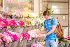 Młody człowiek wybiera świeżych kwiaty jego urocza dziewczyna przy europejczyka rynkiem Zdjęcie Royalty Free
