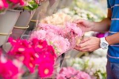 Młody człowiek wybiera świeżych kwiaty jego urocza dziewczyna przy europejczyka rynkiem Zbliżenie rozmaitość i wibrujący kwiaty Zdjęcie Stock