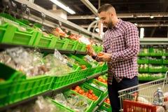 Młody Człowiek Wybiera Świeżych pomidory w supermarkecie obraz royalty free