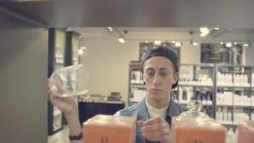 Młody człowiek wybiera świeczkę w piękno sklepie zbiory