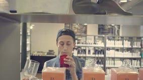 Młody człowiek wybiera świeczkę w piękno sklepie zdjęcie wideo