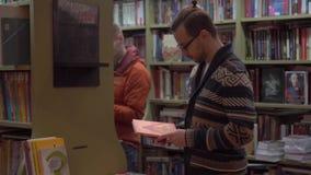 Młody człowiek wybiera książkę w bookstore zdjęcie wideo
