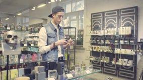 Młody człowiek wybiera pachnidło w piękno sklepie zbiory