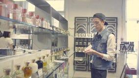 Młody człowiek wybiera pachnidło w piękno sklepie zdjęcie wideo