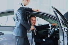 Młody człowiek wybiera samochód przy salonem z pomocą konsultant fotografia royalty free