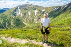 Młody człowiek Wycieczkuje przy Carpathians gór stojakami na górze wzgórza Obraz Stock