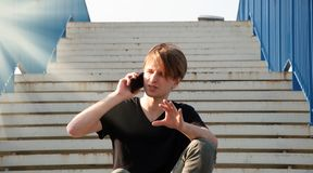 Młody człowiek wyjaśnia coś komplikującego, podczas gdy opowiadający przez telefonu, siedzi na schodkach z błękita ogrodzeniem zdjęcie royalty free
